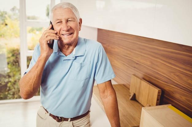 Hombre senior sonriente en una llamada telefónica en la sala de estar