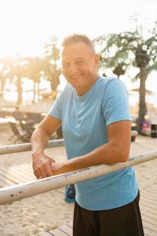 Hombre senior sonriente posando mientras hace ejercicio en el parque