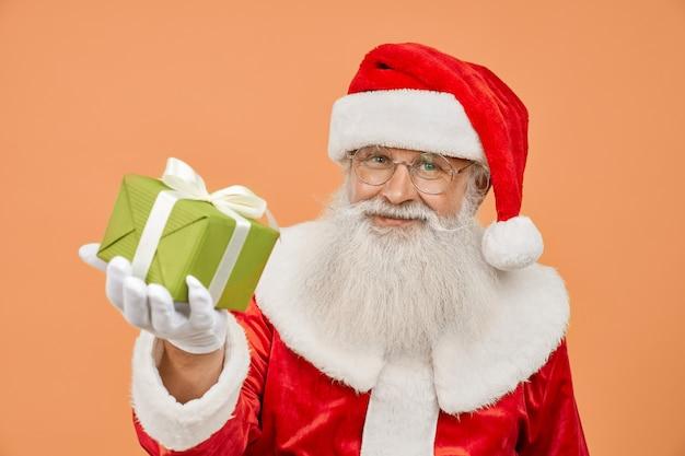 Hombre senior en traje rojo de santa y anteojos sosteniendo una pequeña caja de regalo verde con lazo blanco
