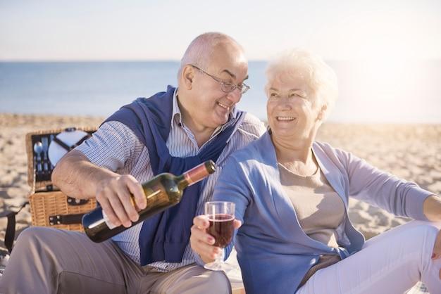 Hombre senior vertiendo vino tinto en la playa, la jubilación y el concepto de vacaciones de verano