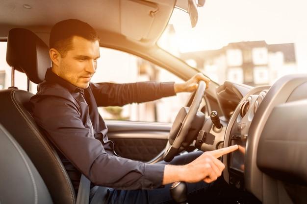 Un hombre está sentado en un auto. vehículo interior. hombre de negocios, conducción