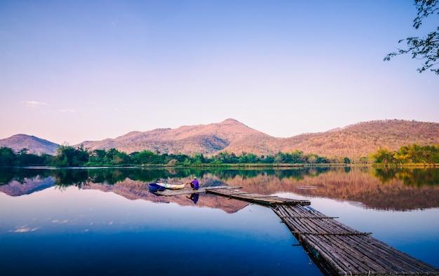 El hombre sentado en una balsa, degustando vistas de la mañana en la presa.