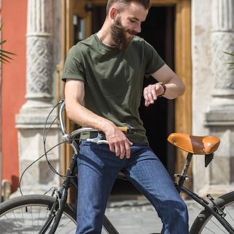 Hombre sentado en bicicleta mirando la hora en el reloj