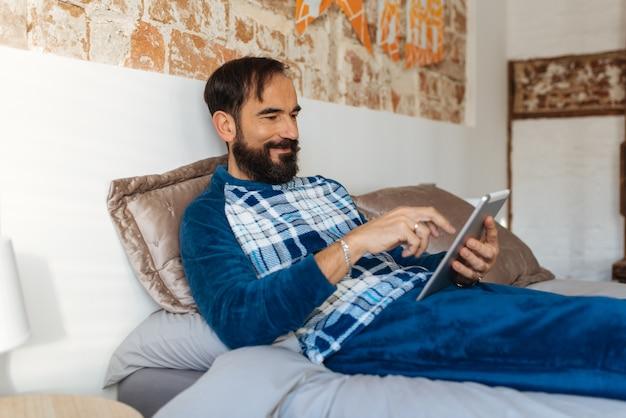 Hombre sentado en la cama relajado en casa sobre la mesa