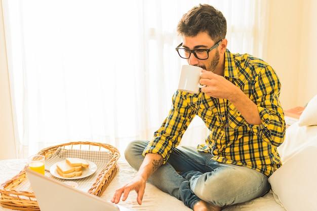 Hombre sentado en la cama tomando un café con el desayuno y una computadora portátil en la cama
