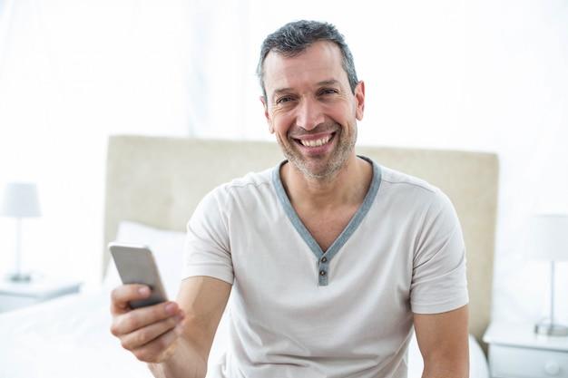 Hombre sentado en la cama y usando teléfono inteligente en el dormitorio