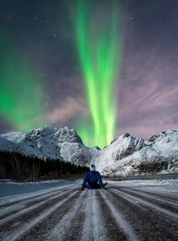 Hombre sentado en una carretera nevada mirando aurora boreal