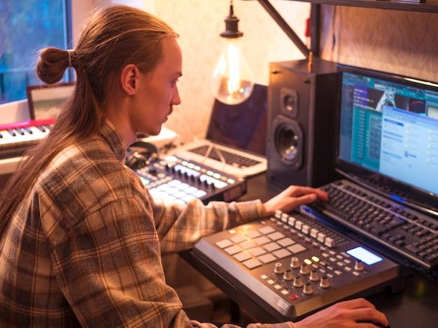 Hombre sentado en casa estudio con equipo de música profesional