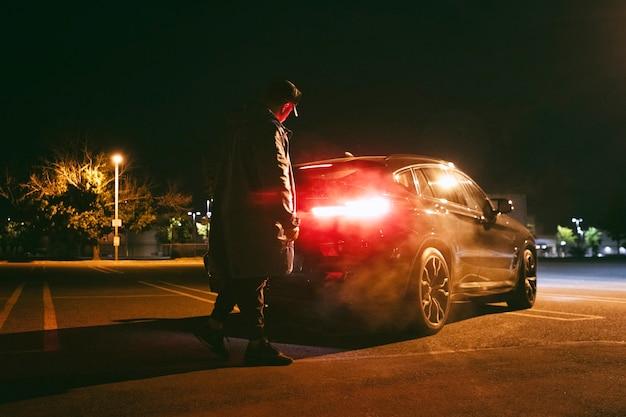 Hombre sentado en el coche por la noche