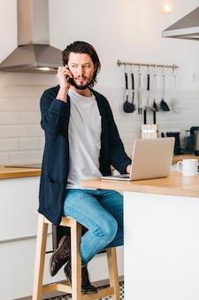 Hombre sentado en la cocina usando una computadora portátil y hablando por teléfono celular mirando a otro lado
