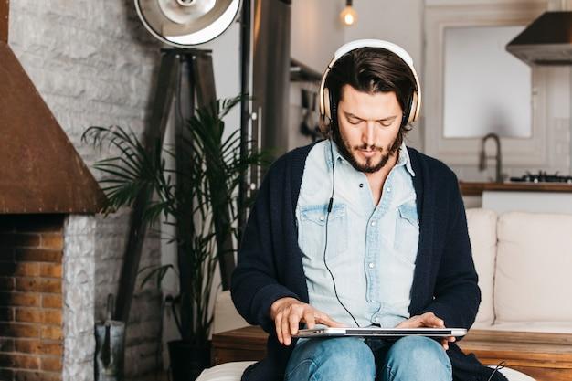 Hombre sentado en la cocina usando una laptop para escuchar música en los auriculares