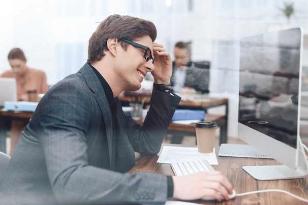 El hombre está sentado en la computadora y trabajando.
