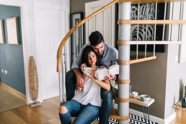 Hombre sentado con su novia sentado en el libro de lectura de la escalera