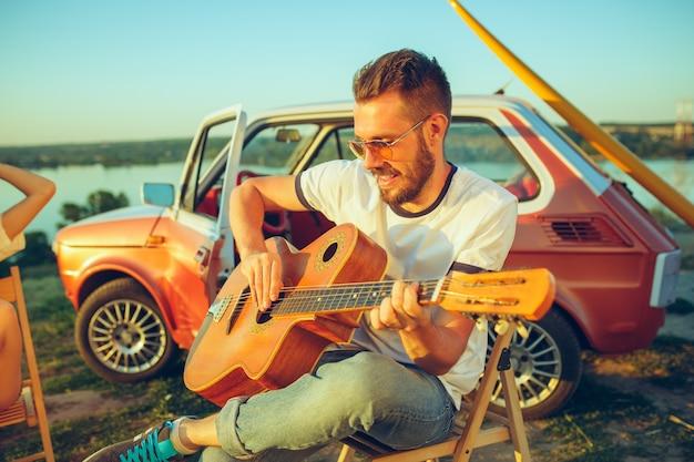 Hombre sentado y descansando en la playa tocando la guitarra en un día de verano cerca del río. vacaciones, viajes, concepto de verano.