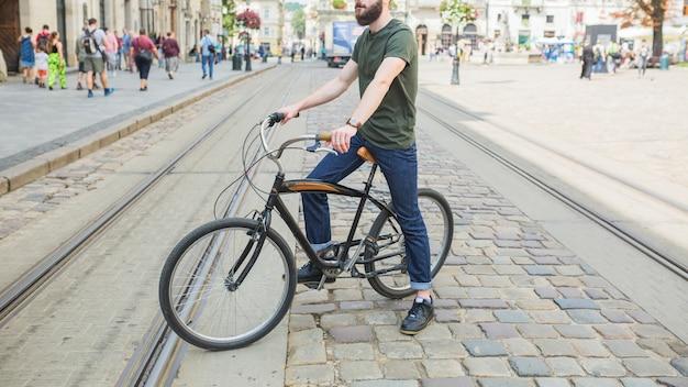 Hombre sentado en bicicleta en la ciudad