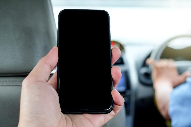 Hombre sentado en el asiento trasero del taxi y mano izquierda sosteniendo el teléfono móvil