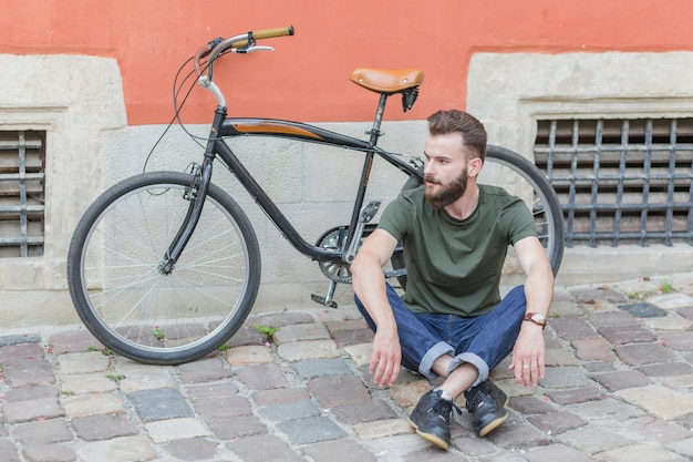 Hombre sentado en el pavimento de piedra frente a la bicicleta