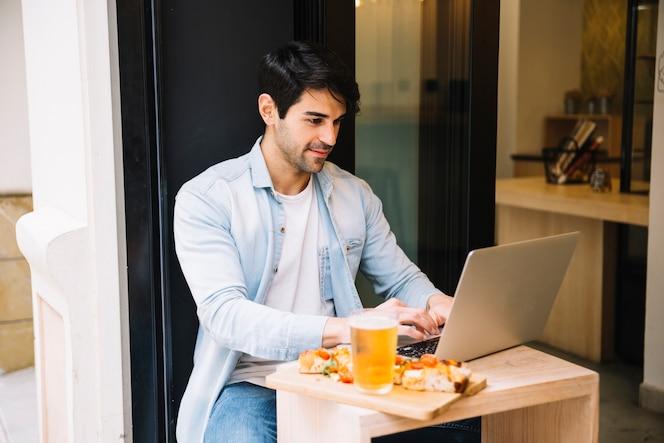 Hombre sentado en la cafetería con la computadora portátil