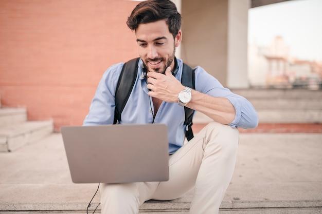 Hombre sentado en la escalera usando la computadora portátil