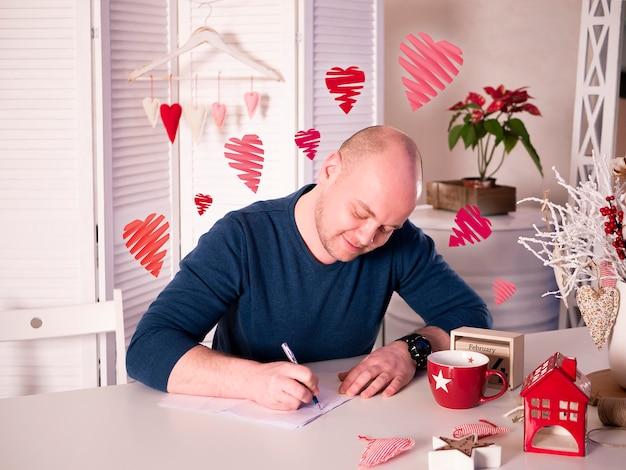 Hombre sentado y escribiendo una carta de amor a su novia en un hermoso y luminoso interior con corazones volando a su alrededor.