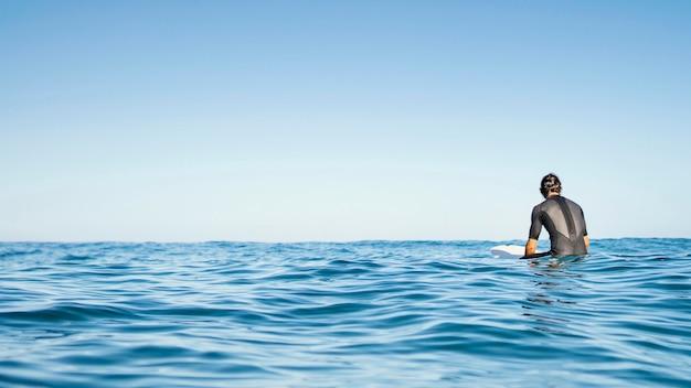 Hombre sentado en el espacio de la copia de agua
