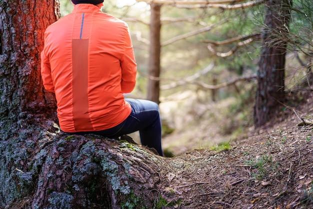 Hombre sentado de espaldas sobre un gran árbol en el paisaje verde, mirando al sol al amanecer.