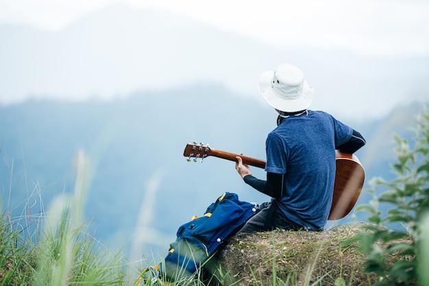 Un hombre sentado felizmente tocando la guitarra en el bosque solo.