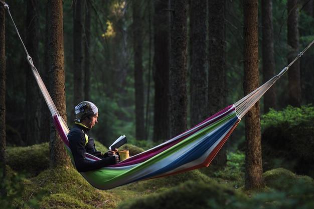 Hombre sentado en una hamaca en un bosque de pinos y leyendo un libro