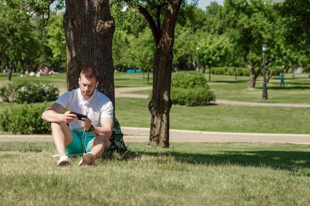 Un hombre está sentado hierba, trabajando un teléfono inteligente en una ciudad parka verde césped al aire libre en la naturaleza