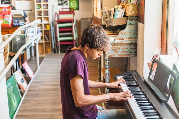 Hombre sentado y jugando sintetizador