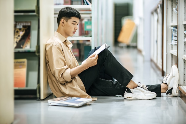 Un hombre sentado leyendo un libro en la biblioteca.