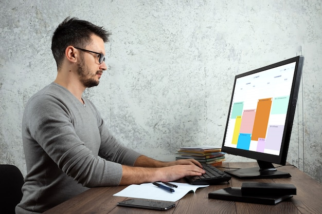 Hombre sentado en una mesa en la oficina, trabajando en una computadora.