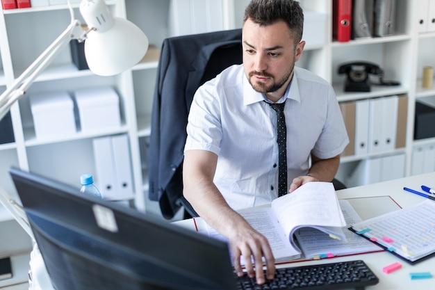 Un hombre está sentado en una mesa en la oficina, trabajando con documentos y una computadora.