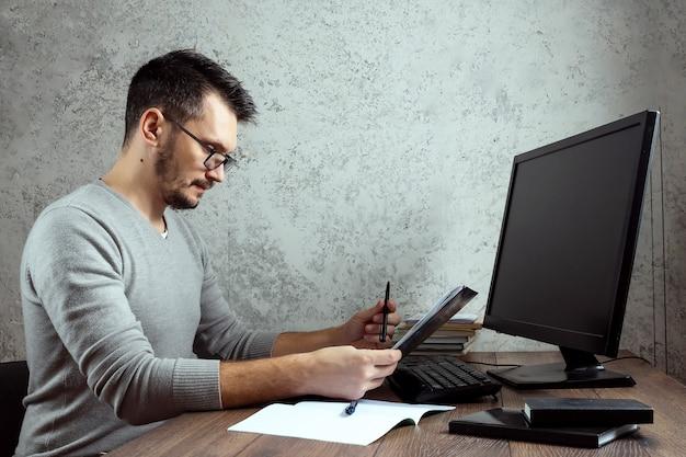 Hombre sentado en una mesa en la oficina, trabajando en papeles importantes.