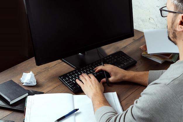 Hombre sentado en una mesa en la oficina