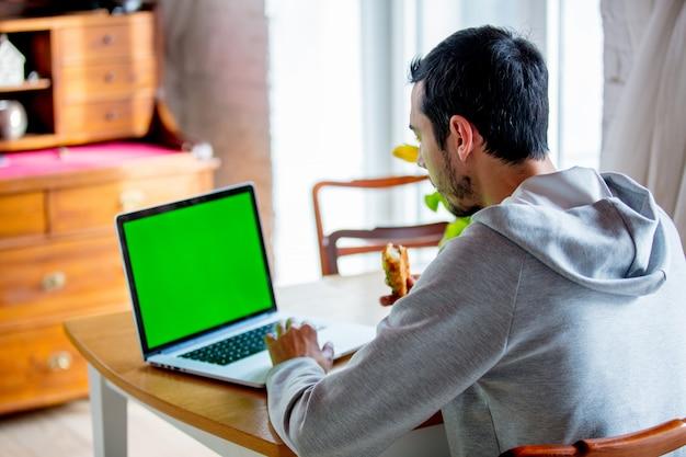 Hombre sentado a la mesa con una taza de café y ordenador portátil.