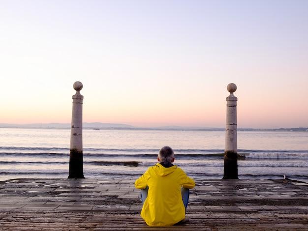 Hombre sentado y mirando el océano al amanecer en cais das colunas, lisboa, portugal