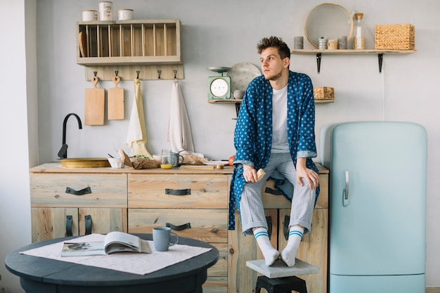 Hombre sentado en el mostrador de la cocina con comida