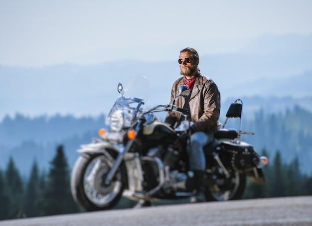 Hombre sentado en la moto de viaje y relajante