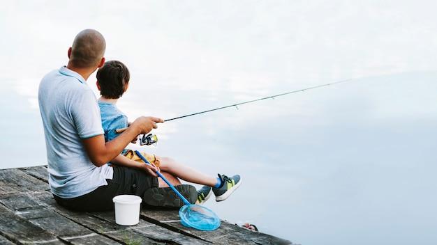 Hombre sentado en el muelle con su hijo pescando en el lago