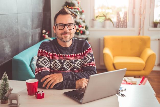 Hombre sentado en la oficina en casa y posando