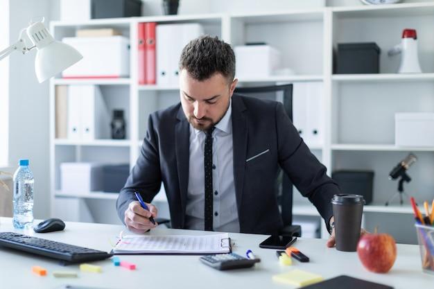Un hombre está sentado en la oficina a la mesa, sosteniendo un vaso de café y un bolígrafo en la mano.