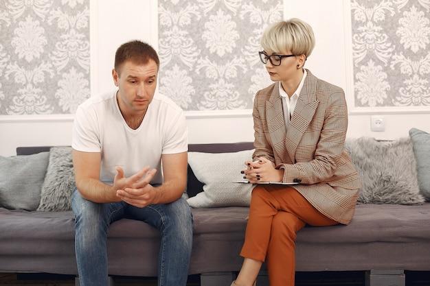 Hombre sentado en la oficina del psicólogo y hablando sobre problemas