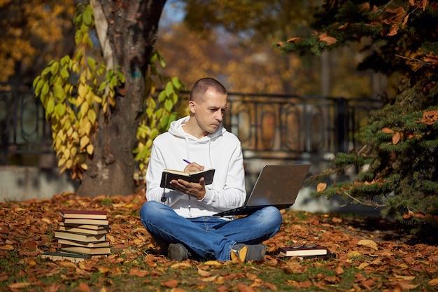 Hombre sentado en el parque con laptop, bloc de notas, libros y libros de texto