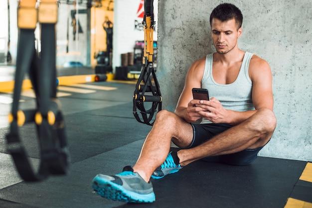 Hombre sentado en el piso usando el teléfono móvil en el gimnasio