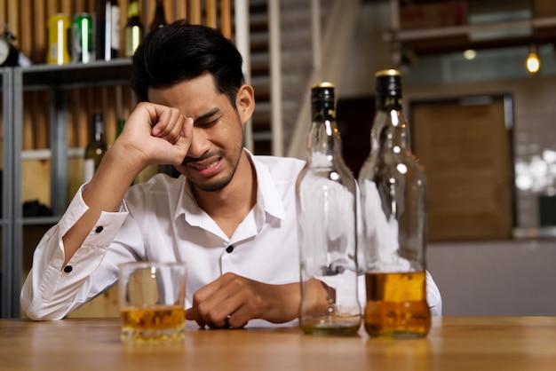 Un hombre sentado en el pub está llorando debido a su tristeza y quiere olvidarlo bebiendo alcohol.