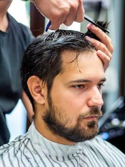 Hombre sentado quieto y cortándose el pelo