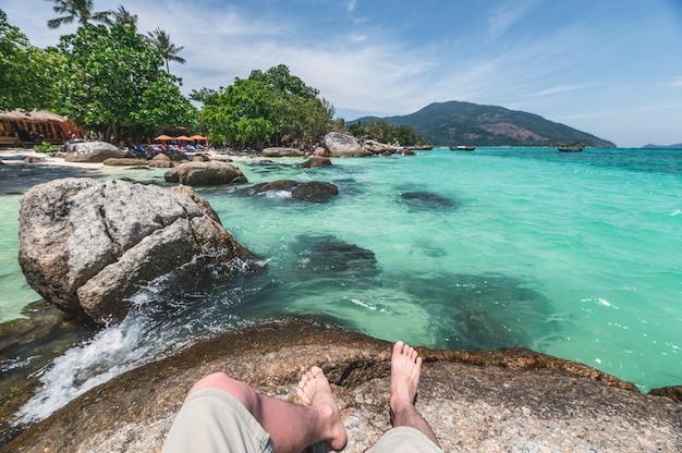 Hombre sentado recreación en piedra en el mar tropical en la isla de lipe
