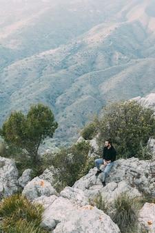 Hombre sentado en roca en la naturaleza