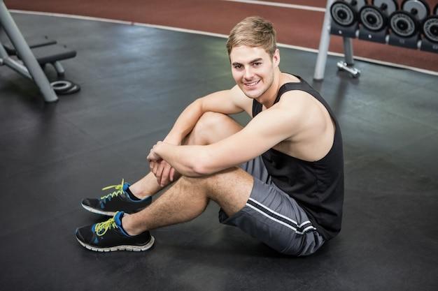Hombre sentado en la sala de pesas sonriendo